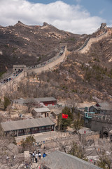 Beijing, China - April 28, 2010: Great Wall of China at Badaling.The wall with people walkling on top and the base village down up front with red Chinese flag.. Mountains on horizon under blue sky.