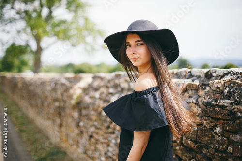 Beautiful Young Sexy Woman Model Of Brunette With Dark Skin In Black Dress And Hat With