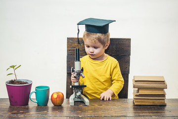 Kid boy with microscope. Smart small boy, scientist child in academic cap works with microscope. Early development, education, enthusiastic pupil concept - cute child standing at table with microscope