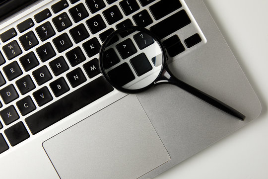 top view of magnifying glass and laptop on grey