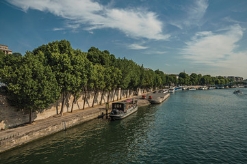 """Seine River bank with walls, greenery and boats under sunny blue sky in Paris. Known as the """"City of Light"""", is one of the most impressive world's cultural center. Northern France."""