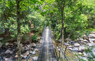 Ponte pênsil sobre rio com pedras