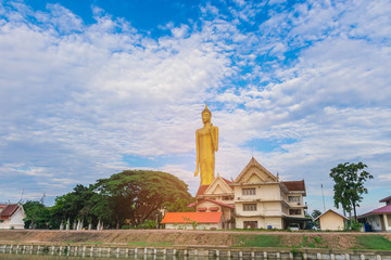 Big Buddha with the beautiful sky cloud, with the beam, light and lens flare effect tone background.The public properties at Wat Burabha Temple, Muang District, Roi Et Province, Thailand.
