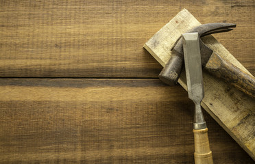 Hammer and Chisel on wood background