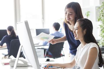 二人の女性たちはパソコン画面を一緒に見ている