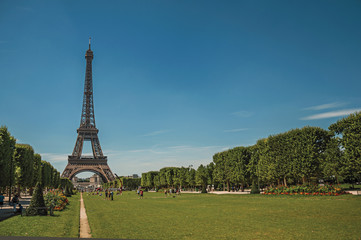 "Overview of stunning Eiffel Tower, people and greenery under sunny blue sky, in Paris. Known as the ""City of Light"", is one of the most impressive world's cultural center. Northern France."