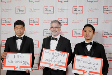 Thura Aung (L), brother of Wa Lone, and Win Khant Kyaw (C), brother in law of Wa Lone, pose with publisher Peter Barbey while holding signs on behalf of detained Reuters journalists Kyaw Soe Oo and Wa Lone at the PEN America Literary Gala in New York