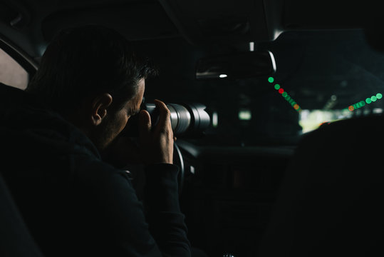 back view of focused man doing surveillance by camera with object glass from his car