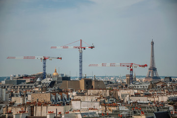 "Close-up of buildings rooftops, cranes and Eiffel Tower on the horizon in Paris. Known as the ""City of Light"", is one of the most impressive world's cultural center. Northern France."