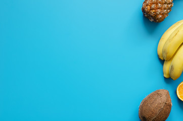 Tropical fruits: banana, coconut, pineapple on blue background
