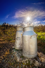Close view of two aluminum milk cans on the roadside in a county Cork