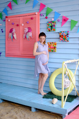 Pregnant young woman standing in blue dress near children houe and holding belly. Concept of motherhood and pregnance.