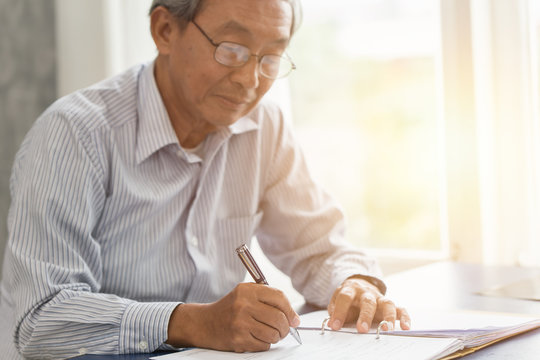 Asian senior working hand writing or sign insurance contract for future concept.