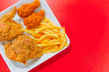 Fried Fast food of Kentucky style fried chicken and French Fries on red background with space for text