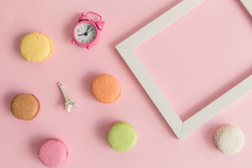 Colorful macaroons, alarm clock, Eiffel Tower miniature and photo frame on pastel pink background abstract concept.