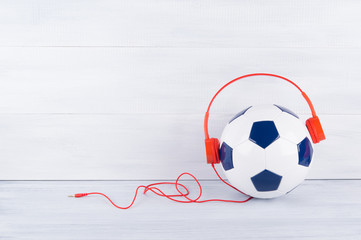 a soccer ball wearing red headphones on a gray background