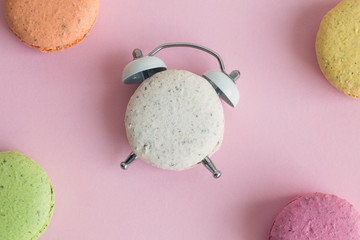 Flat lay of colorful macarons on pastel pink background. One of them in shape of alarm clock.