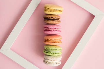 Macaroons and picture frame on rose background