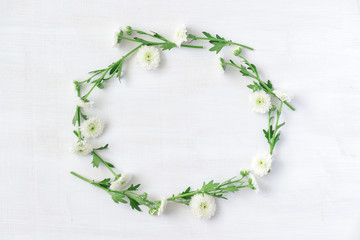 Scenic wreath of white flowers on white wooden background