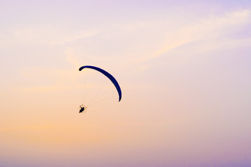 A paraglider flying at sunset sky background, active rest outdoors, extreme sports, extreme sport