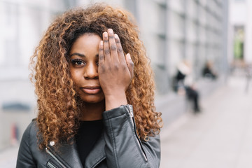 Young African woman covering on eye with a hand