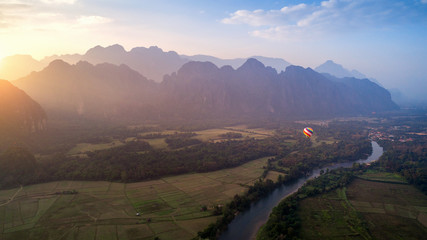 Aerial view of Vang vieng with mountains and balloon at sunset.