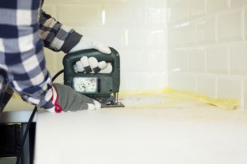 Man cutting kitchen countertop using electric jigsaw. Home improvement, renovation concept.pt
