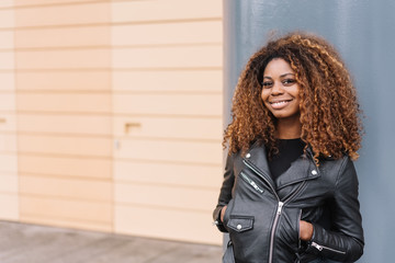 Relaxed trendy African woman in black leather
