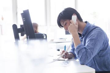 男性はオフィスでクライアントと電話している