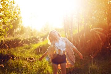 Happy young woman enjoying wonderful evening. Warm weather, summer, field
