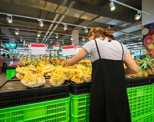 Asian woman buying fresh fruit at the supermarket