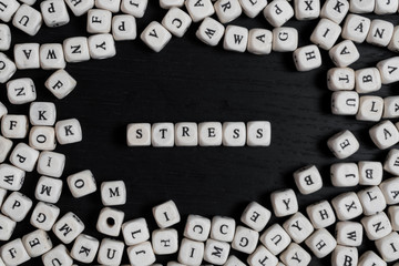 Word STRESS on wooden cubes on a black wooden table with copy space