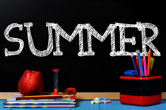 Text Summer on black chalkboard with school accessories