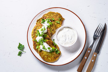 Zucchini pancakes with greens and sour cream on white.