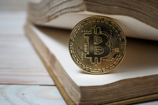 Golden bitcoin on open book electronic or digital money