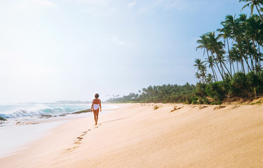 Woman in white swimsuit walks on lonely sand tropical beach