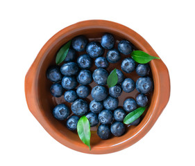 blueberries in a clay plate isolated on a white background. juicy fresh bilberry. top view closeup