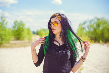 Beautiful woman with green hair posing in Indie or new Hippie style clothes . Outdoor fashion. Cute beautiful girl in boho style
