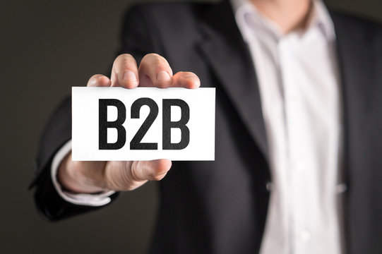 B2B and business-to-business marketing concept. Businessman holding card with text.