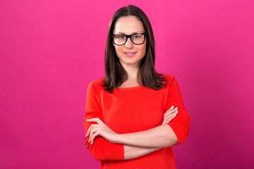 Beautiful brunette woman in glasses on a pink background.