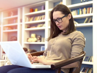 Beautiful brunette woman in glasses working with laptop computer.