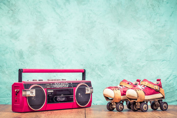 Retro designed radio cassette tape recorder and classic steel children's roller skates pair with red leather sneakers front aquamarine concrete wall textured background. Vintage style filtered photo