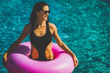 beauty woman with slim figure in black bikini holding rubber ring in the swimming pool. Summer Vacation. Enjoying suntan. Weekend on resort