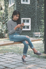 Portrait of beautiful asian woman using her mobile phone and sitting on wood swing under tree.
