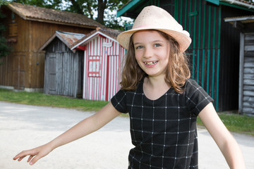 Beautiful little girl child wearing a spring black dress and straw hat in hut wood village