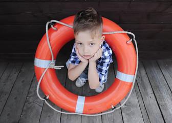 Sad little boy sitting on the wood floor with a lifebuoy