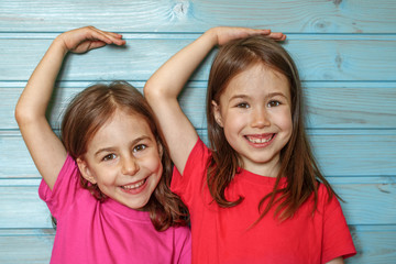Girls measure each other's growth against a blue wooden wall