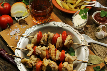 fried chicken meat with tomatoes on wooden sticks. Barbecue with vegetables on a wooden background.
