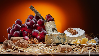 Different types of cheese, vintage knife and fork for cheese and grapes. Dark background. Place for text