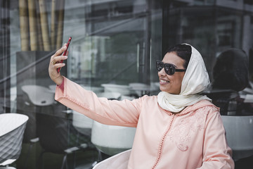 Nice Moroccan woman with hijab.taking a selfie